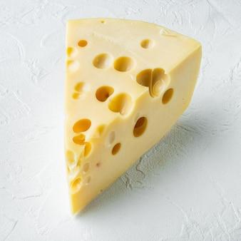 Maasdam-käse auf weißem stein