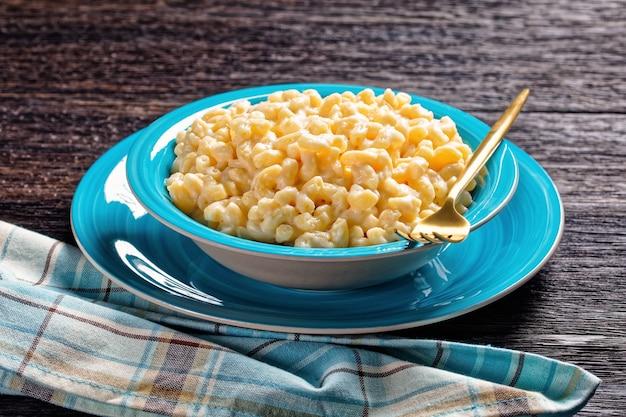 Mac und käse in einer blauen schüssel mit goldener gabel und serviette auf einem holztisch, horizontale ansicht von oben