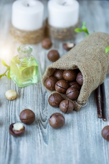 Macadamia-kerne, walnussöl, auf holz