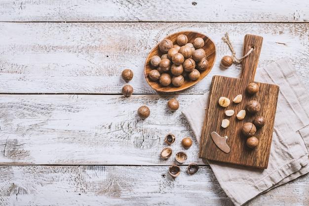 Macadamia-nüsse auf schneidebrett über weißer hölzerner tischoberansicht
