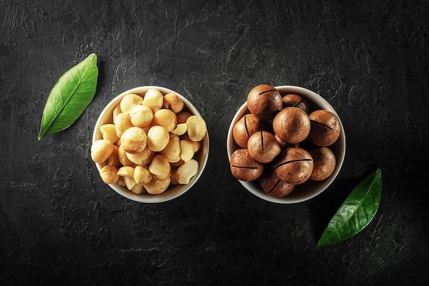 Macadamia-nüsse in weißen schalen auf einer dunklen betonoberfläche draufsicht