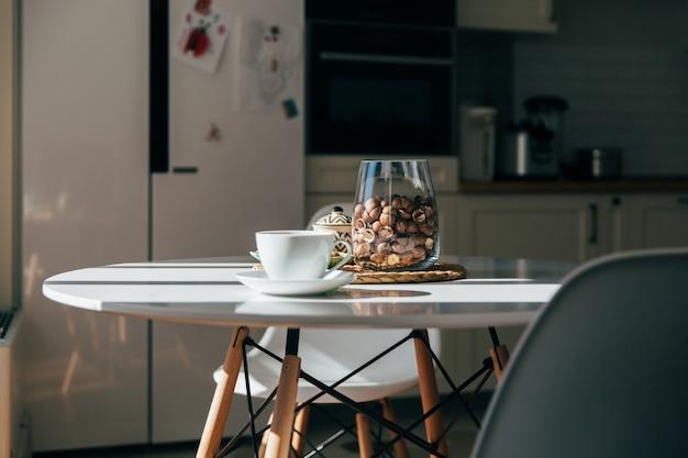 Macadamianüsse in einer schüssel und eine tasse tee oder kaffee stehen im küchentisch, hartes morgenlicht