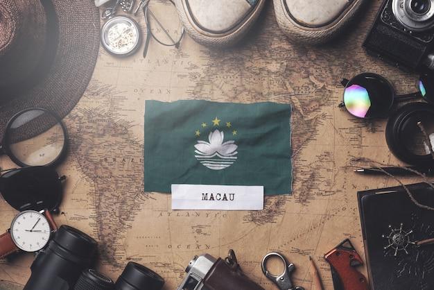Macao-flagge zwischen dem zubehör des reisenden auf alter weinlese-karte. obenliegender schuss