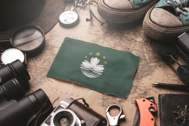 Macao-flagge zwischen dem zubehör des reisenden auf alter weinlese-karte. touristisches bestimmungsort-konzept.