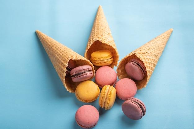 Macarons ergossen sich aus gebäckkegeln auf der draufsicht der blauen oberfläche