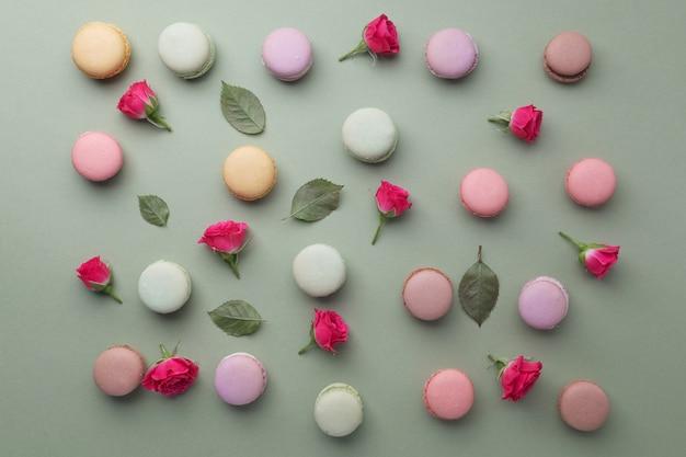 Macarons flach lag mit rosen und blättern auf grünem hintergrund. draufsicht