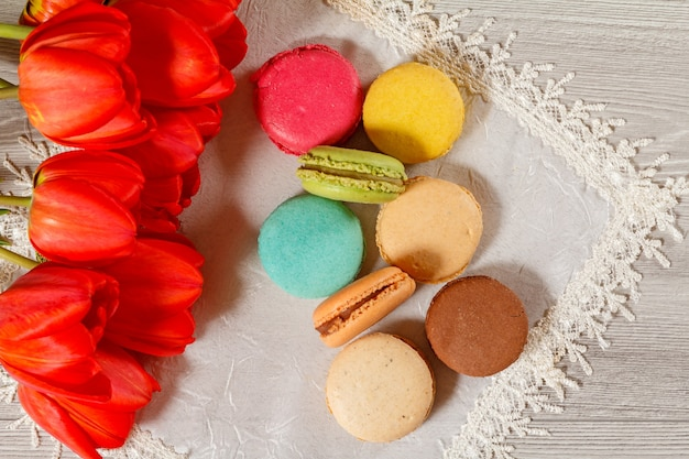 Macarons kuchen unterschiedlicher farbe auf seidenserviette mit strauß frischer roter tulpen mit holzhintergrund. ansicht von oben
