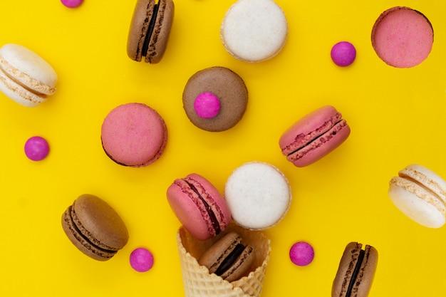 Macarons kuchen. waffelkegel mit makronen auf gelbem hintergrund. flach liegen.