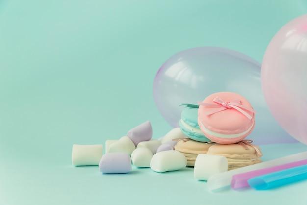 Macarons; marshmallow; ballons auf türkisfarbenen hintergrund