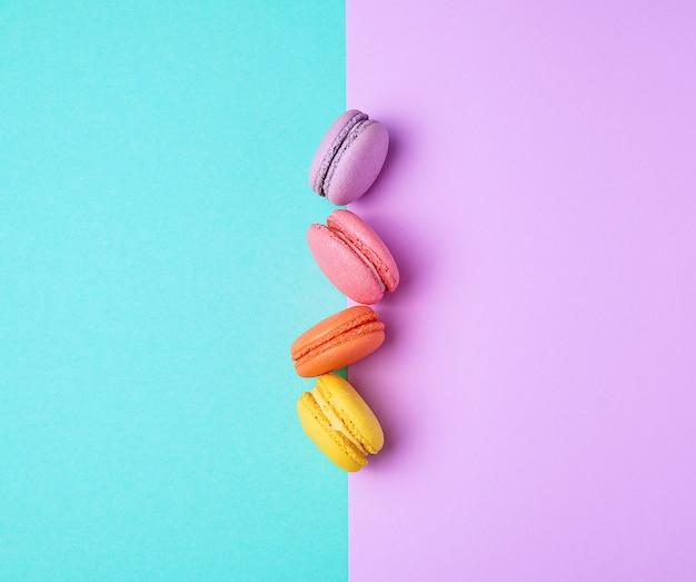 Macarons mit sahne auf einem purpurroten grünen hintergrund