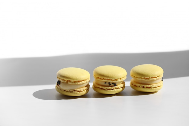 Macarons mit schatten vom fenster auf weißem hintergrund