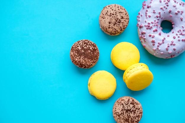 Macarons und schaumgummiringe auf blauem süßigkeitshintergrund.