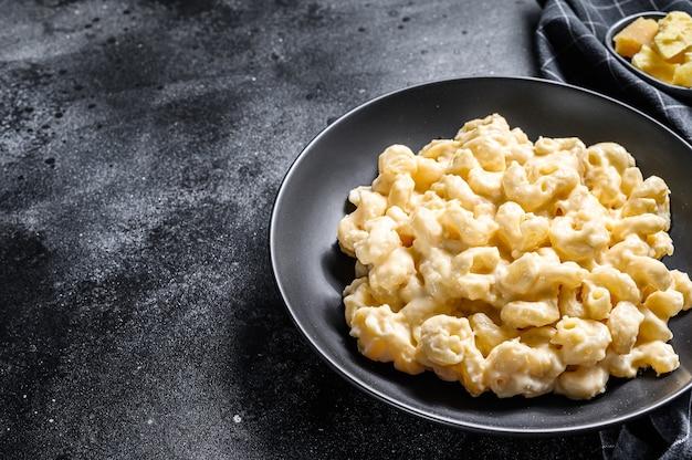 Maccaroni und käse. makkaroni-nudeln nach amerikanischer art in käsesauce. schwarzer hölzerner hintergrund. draufsicht. speicherplatz kopieren.