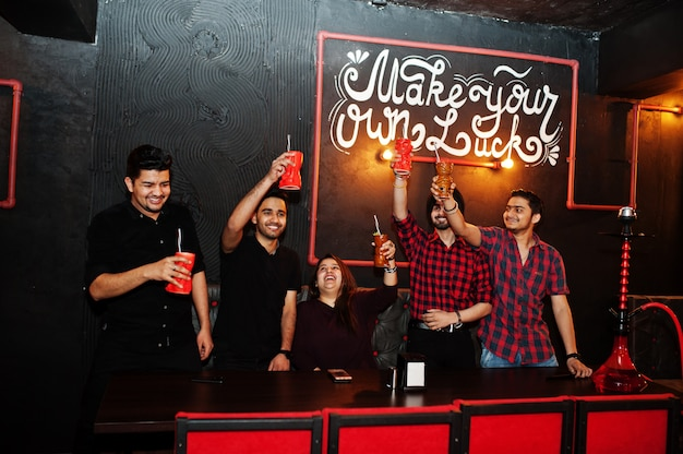 Mach dein eigenes glück! gruppe von freunden, die spaß haben und sich im nachtclub ausruhen, cocktails trinken, jubeln und shisha rauchen