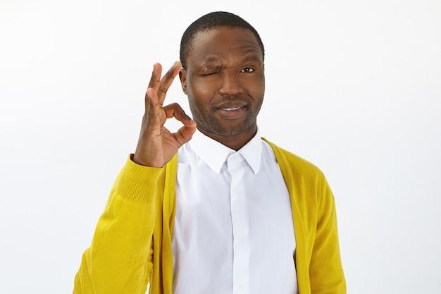 Mach dir keine sorgen, alles wird gut. hübscher junger afroamerikaner mit borsten, die in die kamera blinken und eine gute geste als zeichen der zustimmung, der positiven einstellung und der positiven einstellung machen, die gute gefühle ausdrückt