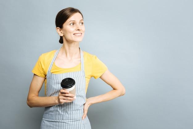 Mach eine pause. positiv entzückte brünette, die ein lächeln auf ihrem gesicht hält und einen pappbecher hält, während sie zur seite schaut