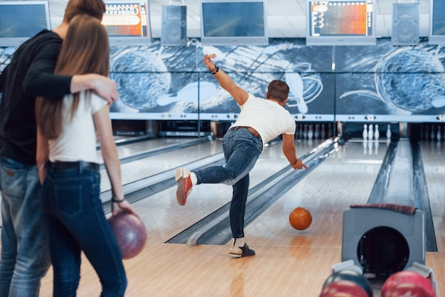 Mach es mit leichter kraft. junge fröhliche freunde haben an ihren wochenenden spaß im bowlingclub