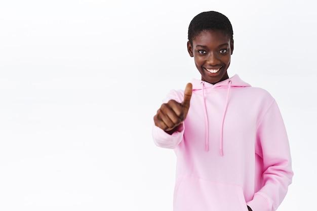 Mach mit, klingt cool. glückliches und zufriedenes afroamerikanisches mädchen mit kurzen haaren in rosa hoodie, hand mit daumen nach oben ausstrecken und lächeln