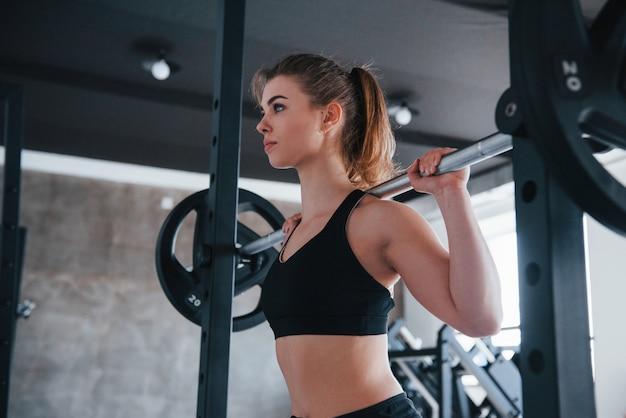 Mach weiter so. foto der herrlichen blonden frau im fitnessstudio zu ihrer wochenendzeit