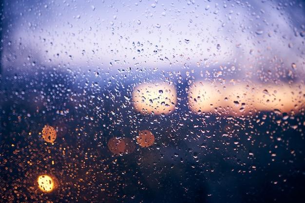 Machen sie das fenster mit dem hintergrund der abendlichen stadtansicht nass