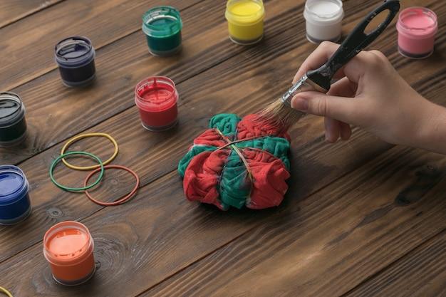 Machen sie ein mädchen-t-shirt im tie-dye-stil in grün und rot. färben von stoff im tie-dye-stil.