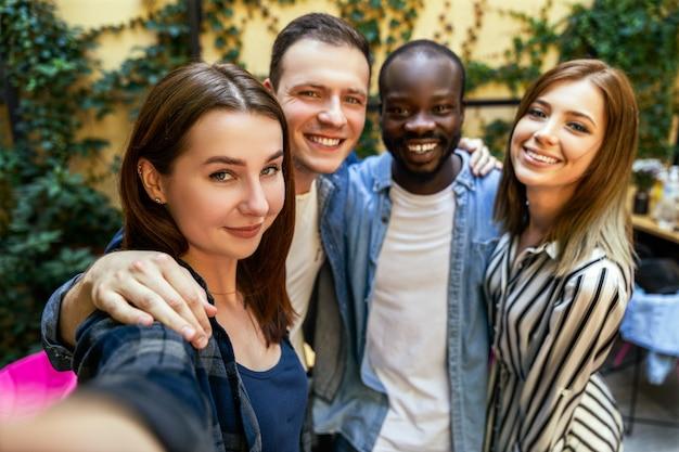 Machen sie ein selfie-foto mit den besten freunden am warmen frühlingstag im gemütlichen restaurant