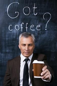 Machen sie eine pause! selbstbewusster älterer mann in formeller kleidung, der kaffeetasse ausstreckt und lächelt, während er gegen eine tafel mit kreidezeichnung darauf steht