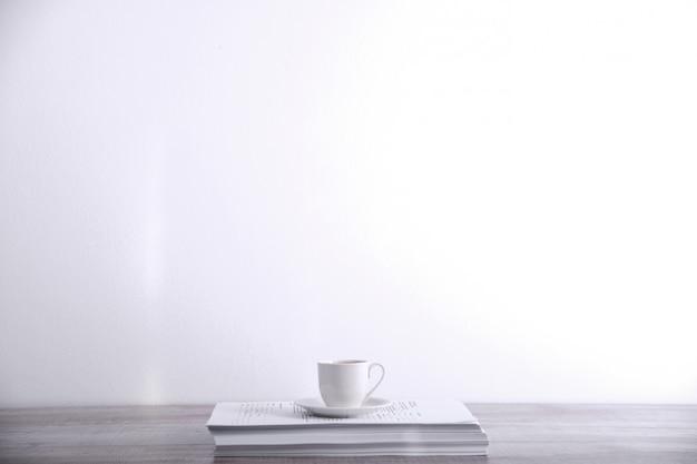 Machen sie eine pause, trinken sie ein kaffeekonzept. tasse kaffee auf einem stapel papier auf dem tisch