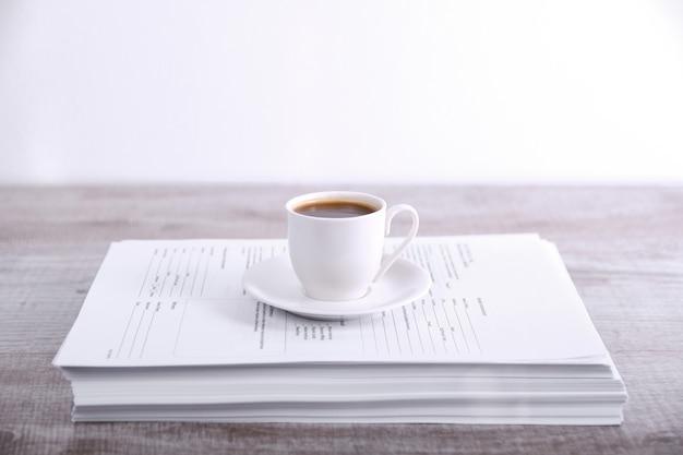 Machen sie eine pause, trinken sie kaffee-konzept. tasse kaffee auf einem stapel papier auf dem tisch