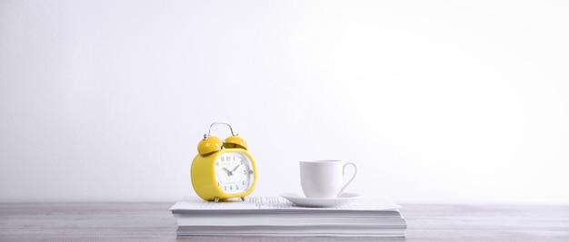 Machen sie eine pause, trinken sie kaffee-konzept. tasse kaffee und uhr auf einem stapel papier auf dem tisch