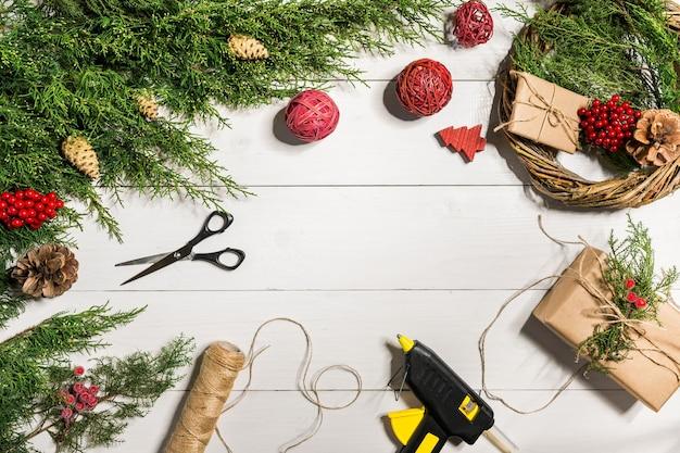Machen sie einen weihnachtskranz mit ihren eigenen händen. fichte zweig, weihnachtskranz und geschenke auf einem weißen hintergrund aus holz. arbeitsplatz für die vorbereitung handgemachter dekorationen. weihnachten und silvester