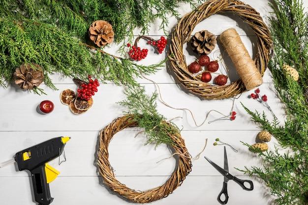 Machen sie einen weihnachtskranz mit ihren eigenen händen fichtenzweig weihnachtskranz und geschenke auf einem weißen holz...