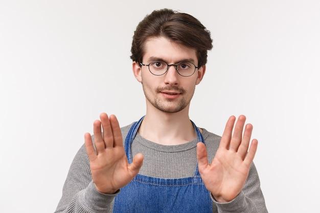 Machen sie es langsamer. nahaufnahmeporträt des ernst aussehenden selbstbewussten jungen männlichen coffeeshop-managers, des mitarbeiters, der ruhige person versucht, stopp oder einfaches zeichen zeigt, kamera schauen