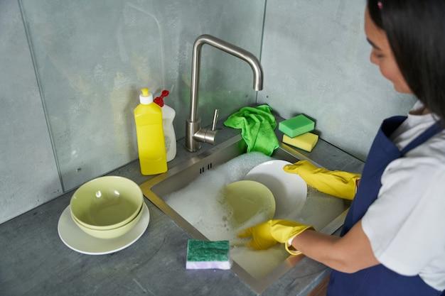 Machen sie es sauber, junge putzfrau in gelben handschuhen, die mit einem schwamm geschirr spült