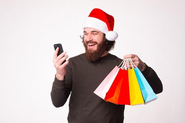 Machen sie ihre einkäufe online über ihr telefon. bärtiger mann hält einige einkaufstüten.