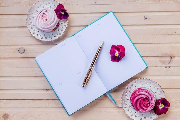 Machen sie pläne in winzigen notizbuch für weihnachten.dekorationen und süße rosa marshmallows.farbener zephyr auf holzwand.wöchentlicher planer oder liste mit stift zu tun. urlaubskonzept planen