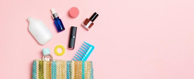 Machen sie produkte, die aus kosmetiktasche auf rosa pastellhintergrund mit leerem raum für ihr design verschütten