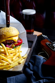 Machen sie rindfleischburger und pommes-frites auf tabelle im restaurant mit glas bier auf dunkelheit in handarbeit. moderner schnellimbissmittagessenrahmen