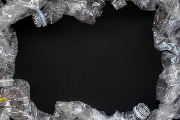 Machen sie sich mit dem thema umweltschutz vertraut. komprimierte plastikflaschen auf einem schwarzen hintergrund.