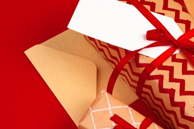 Machen sie weihnachtsgeschenke mit roten bändern auf verziertem weihnachten in handarbeit