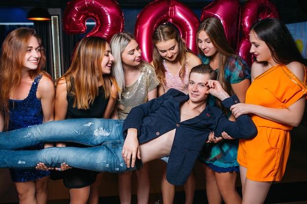Macho auf der neujahrsparty. sexuelle andeutungen, lustvolle weibliche gesellschaft. verführerischer junger mann, lustiger hintergrund, verführungs- und abholkonzept