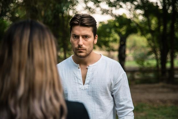 Machomann sieht seine freundin in einem park vorwurfsvoll an.