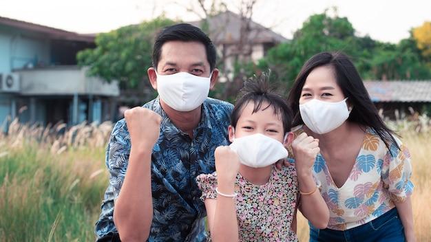 Macht der familie mit vater, mutter und tochter, die eine medizinische gesichtsmaske tragen, um 2019 zu schützen - ncov, covid 19 oder corona-virus. bleiben sie zu hause konzept