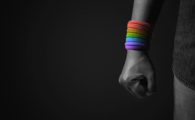Macht, protest und ausdruck für lgbtq, rechtekonzept. nahaufnahme von faust und regenbogen-handschlaufe. wütend, bereit zu schlagen. zugeschnittener und selektiver fokus