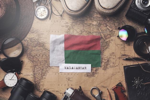 Madagaskar-flagge zwischen dem zubehör des reisenden auf alter weinlese-karte. obenliegender schuss