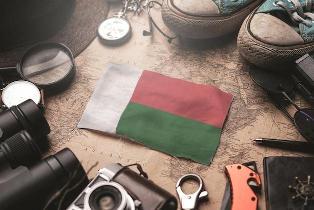Madagaskar-flagge zwischen dem zubehör des reisenden auf alter weinlese-karte. touristisches bestimmungsort-konzept.