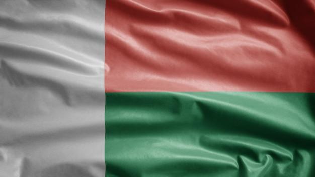 Madagassische flagge weht im wind. madagaskar-banner weht weiche seide. stoff textur fähnrich hintergrund. verwenden sie es für das konzept für nationalfeiertage und länderfeiern