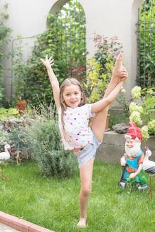Mädchen, das ihr Bein steht im Garten ausdehnt