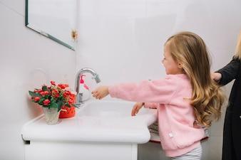 Mädchen, das ihre Hand in der Badezimmerwanne wäscht