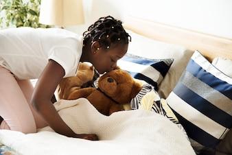 Mädchen des jungen jugendlich, das einen Teddybären küsst